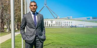 Benson Saulo standing on the lawns in front of Parliament House, Canberra